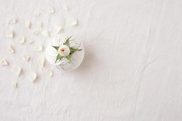 Handgemachtes makramee-geflecht und baumwollfäden mit rosenblüte auf weißem strukturiertem hintergrund, ansicht von oben