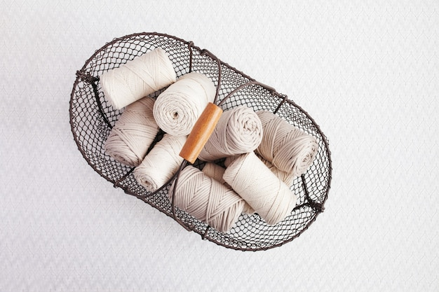 Handgemachtes makramee-geflecht und natürliche baumwollfäden in einem korb auf weißem hintergrund mit schatten