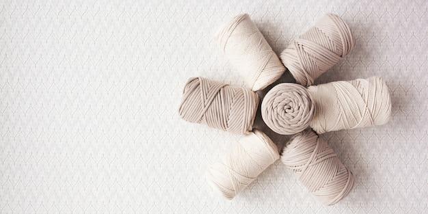 Handgemachtes makramee-geflecht und natürliche baumwollfäden stapeln sich auf weißem hintergrund mit schatten