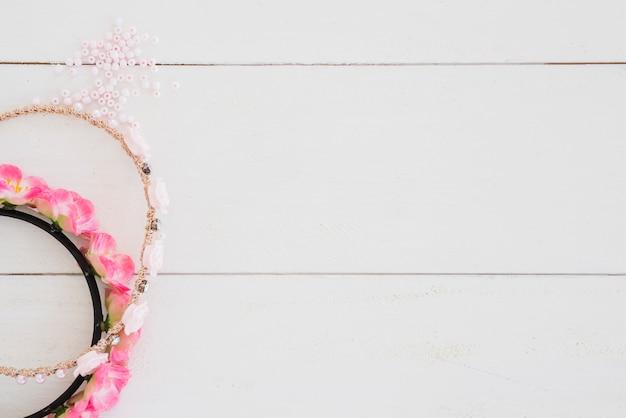 Handgemachtes rosafarbenes haarband und perlen auf weißem hölzernem schreibtisch