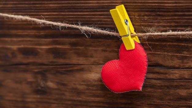 Handgemachtes rotes herz, das mit einer wäscheklammer am seil befestigt ist. valentinstagskarte