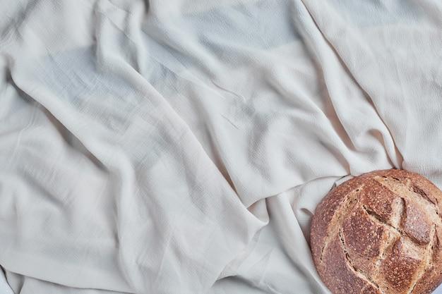 Handgemachtes rundes brot auf einer weißen tischdecke.