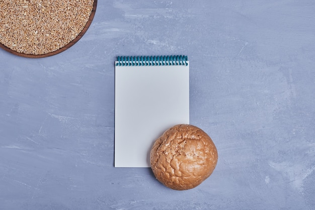 Handgemachtes rundes brot mit einem rezeptbuch beiseite.