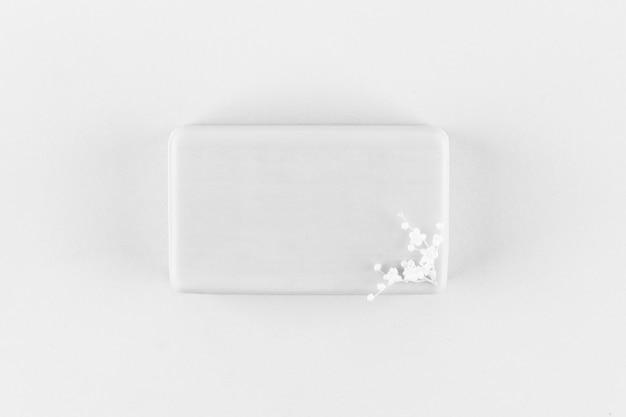 Handgemachtes seifenstück mit kleinen weißen blüten auf hellgrauem hintergrund draufsicht, monochromes foto