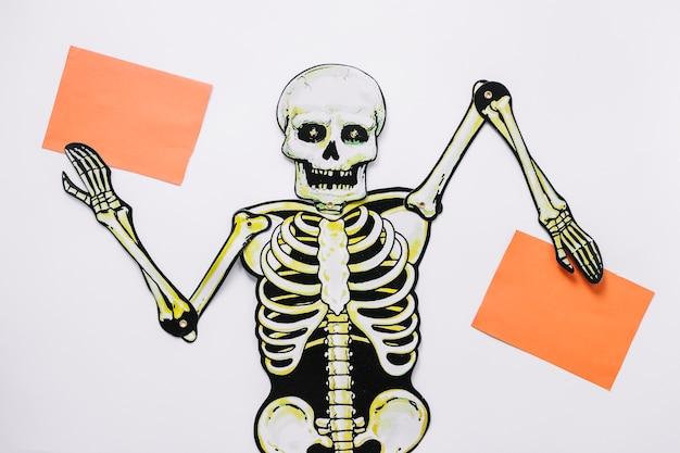 Handgemachtes skelett mit zwei blättern papier