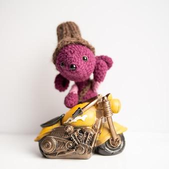 Handgemachtes strickspielzeug. eine ratte mit einem gelben motorrad gehäkelt
