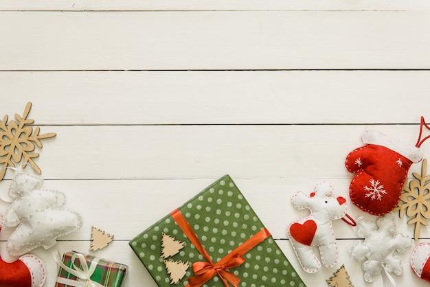 Handgemachtes weihnachtsgeschenk mit spielzeug und dekor auf weißem holzbart