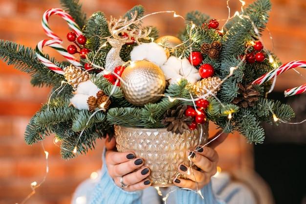 Handgemachtes weihnachtsgeschenk. nahaufnahme topf mit tannenzweigen, zuckerstangen, kugeln und lichterketten in den händen der dame.