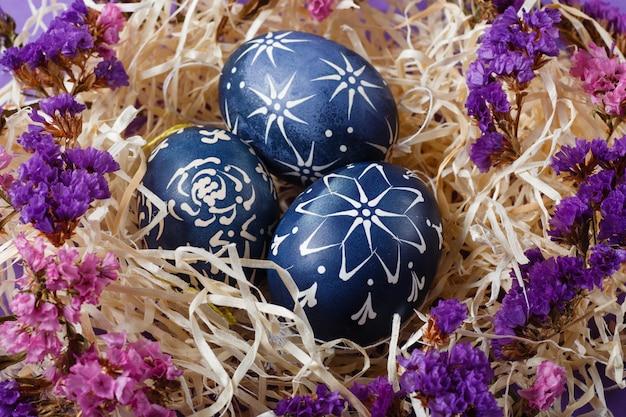 Handgemalte dunkelblaue ostereier im nest und blumen auf violettem backgroud