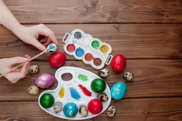 Handgemalte ostereier, farben und pinsel auf hölzernem hintergrund. vorbereitung auf den urlaub. mädchenhände zeichnen ein muster