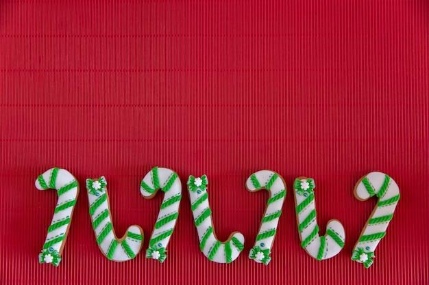 Handgemalte weihnachts-lebkuchengrün und weiße zuckerstange und schneeflocken auf einem schönen roten hintergrund. kartenkonzept. draufsicht. flach liegen.