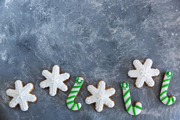 Handgemalte weihnachtslebkuchengrün und weiße zuckerstange und schneeflocken auf einem schönen grauen hintergrund. kartenkonzept. draufsicht. flach liegen.