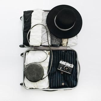 Handgepäck mit stilvoller damenkleidung auf weißem hintergrund. flache lage, ansicht von oben