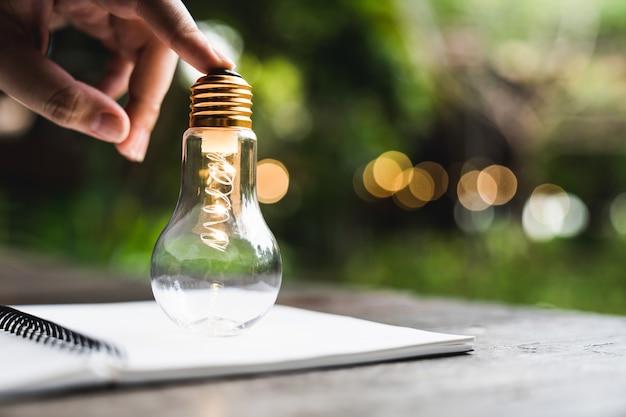 Handgeschäftsmann, der eine glühbirne hält, die auf dem notebook steht. alternative energie, idee, stromsparinnovation und inspirationskonzepte.