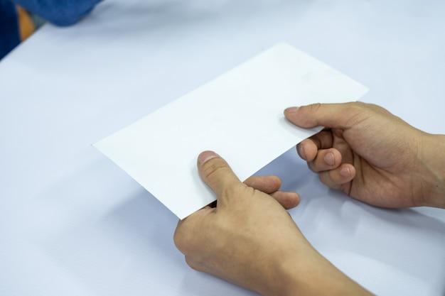Handgeschäftsmann, der leeres weißes umschlagdokument gibt