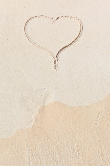 Handgeschriebenes herz im sand mit welle, die sich im strand nähert