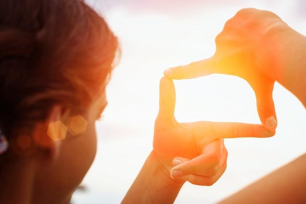 Handgestaltende ansicht entfernt über sonnenuntergang
