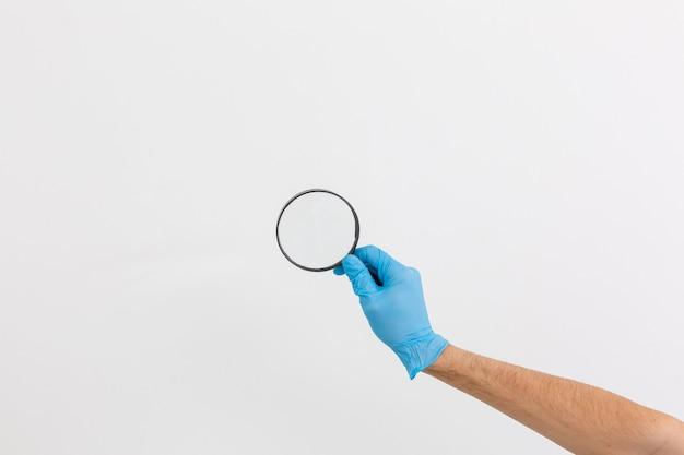 Handgeste in einem blauen medizinischen handschuh mit einer lupe isoliert, nahaufnahme, selektiver fokus, weißer hintergrund