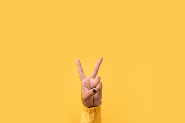 Handgeste v zeichen über gelbem raum