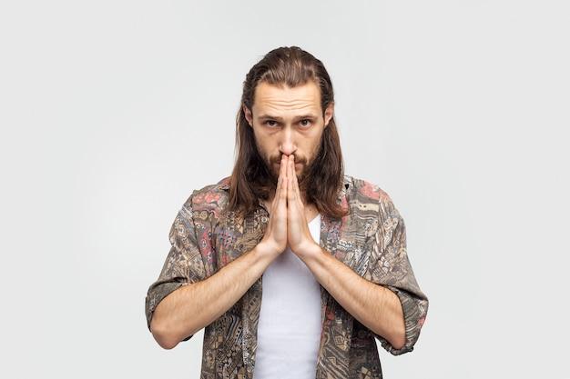 Handgestengebet, bittet um etwas höheres, hoffnung und dankbarkeit. stilvoller sorgloser mann des hipster-reisenden auf einem weißen studiohintergrund, menschenlebensstil