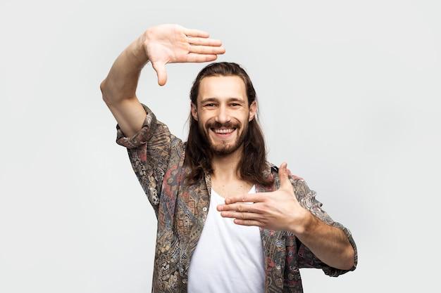 Handgestenrahmen, konzentriert die aufmerksamkeit und konzentriert sich auf sich selbst. stilvoller sorgloser mann des hipster-reisenden auf einem weißen studiohintergrund, menschenlebensstil