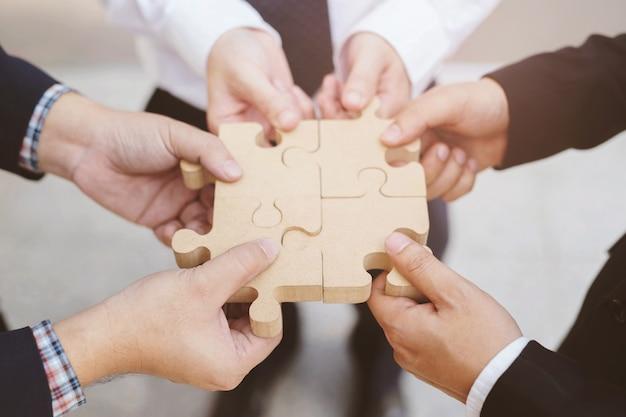 Handgriff mit drei geschäftsmännern, der versucht, hölzernes puzzlestück des puzzlen anzuschließen. ein teil des ganzen. symbol der assoziation und verbindung. erfolgs- und geschäftslösungsstrategie