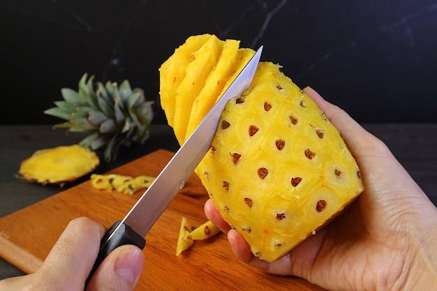 Handhaltemesser zum schälen und entfernen der harten und stacheligen augen einer frischen reifen ananas