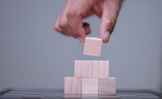 Handhalten und anordnen von holzblockstapeln als stufentreppe mit platz für ihren inhalt im holzblock