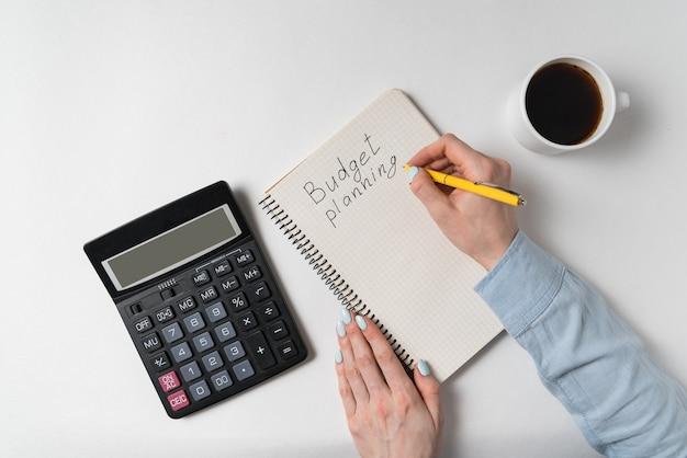 Handhaltestift mit taschenrechner und tasse kaffee. budgetplanungskonzept.