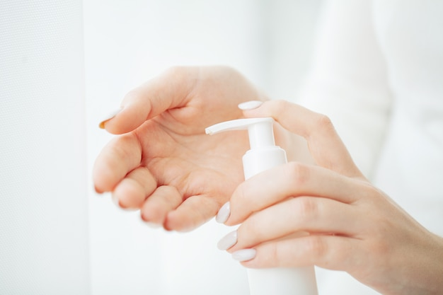 Handhautpflege, abschluss oben von den weiblichen händen, die cremerohr, schönheits-hände mit den natürlichen manikürenägeln auftragen kosmetische handcreme auf weicher seidiger gesunder haut halten