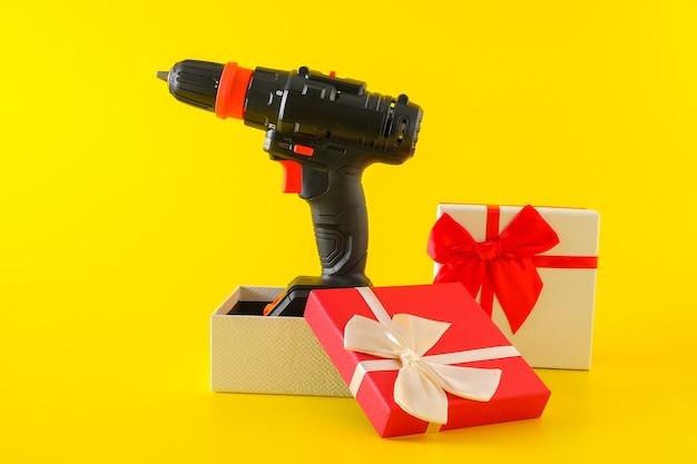 Handheld-akku-bohrmaschine, handbatterie-schraubendreher in geschenkbox. konzept der geschenküberraschung für männer, kopierraum
