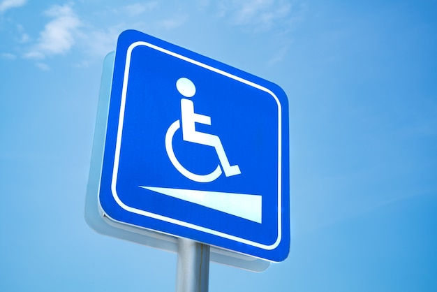 Handicap-zeichen. weißes symbol über blauem hintergrund auf hintergrund des blauen himmels