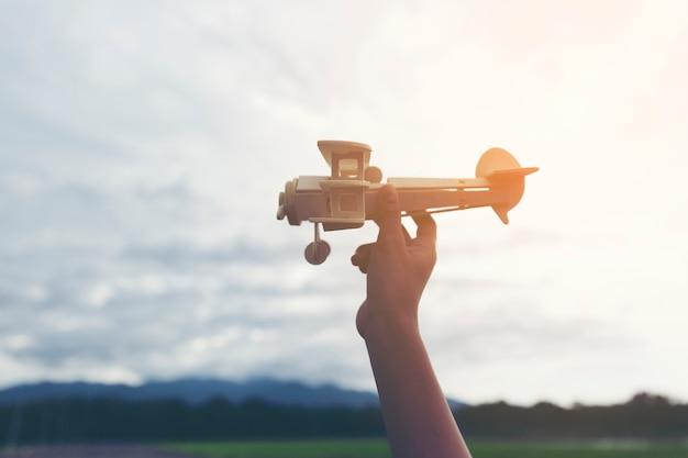 Handjunge mit seiner hand lässt das modell des flugzeuges in die himmelsturmwolke laufen.