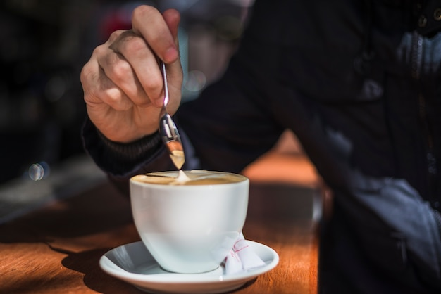 Handkaffee einer person, die lattekaffee mit löffel in der weißen kaffeetasse auf holztisch rührt
