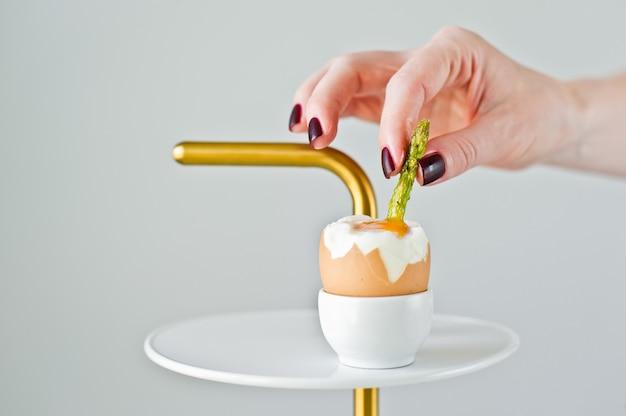 Handkoch fügt ein rinnsal spargel in ein gekochtes ei