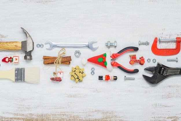 Handliche bauwerkzeuge mit weihnachtsverzierungen auf holz