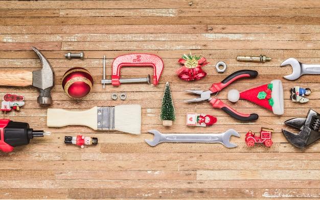 Handliche werkzeuge des baus mit weihnachtsverzierung auf holz
