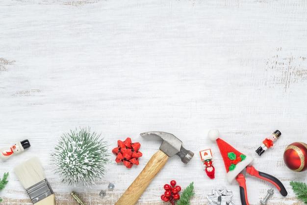 Handliche werkzeuge des baus mit weihnachtsverzierung auf weißem holz