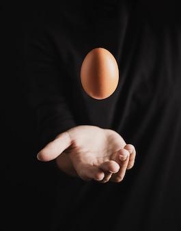 Handlicher bäcker, der ei in einer luft wirft