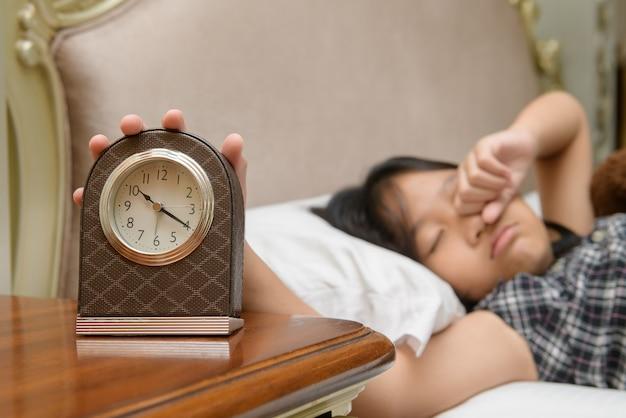 Handmädchen, das nach wecker greift, faul und spätes konzept aufwacht
