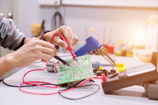 Handmänner halten werkzeug repariert elektronik.