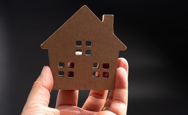 Handmann, der hölzernes modellhaus hält. konzept des hochbaus und der renovierung von häusern.