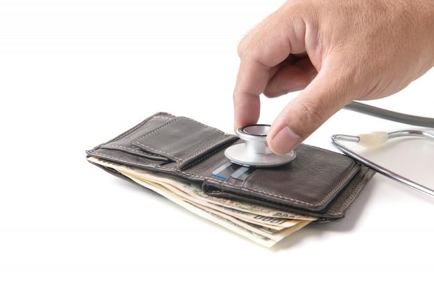 Handmann, der offene geldbörse mit stethoskop überprüft