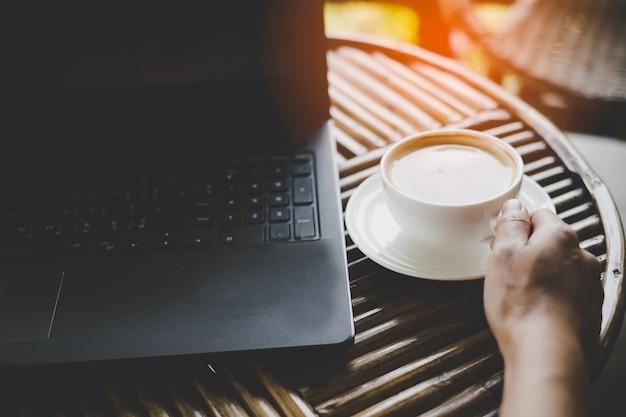 Handmann mit laptop-computer lese nachrichten am morgen im caféladen