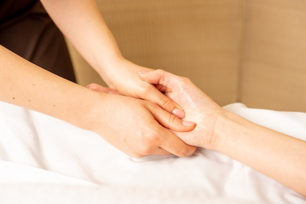 Handmassage. physiotherapeut drückt bestimmte stellen auf die weibliche handfläche.