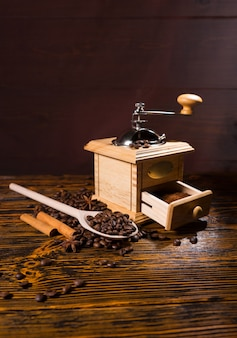 Handmühle und holzlöffel mit kaffeebohnen