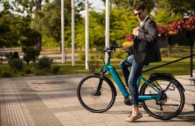 Handosme junger geschäftsmann auf dem e-bike an der straße