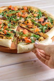 Handpflücken ein stück pizza mit garnelen, muscheln und lachs