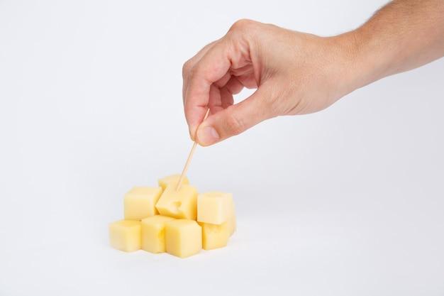 Handpiercing gewürfelten käse mit zahnstocher