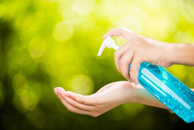 Handpressflasche blaues alkoholgel oder haargel auf grünem bokeh naturwand schönheitsgesundheitspflege schützen corona-virus covid 19